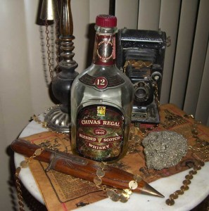 The first bottle of booze I ever bought at a liquor store was Chivas Regal. This particular bottle is from 1955. The Gold nugget next to it is a chunk of fool's gold my old man dug up in the Nevada desert in 1963.